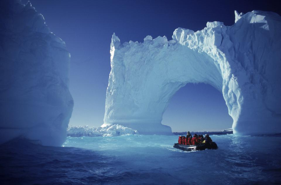 A rubber Zodiac boat with about a dozen people in red jackets floats next to a massive arch apparently made of ice