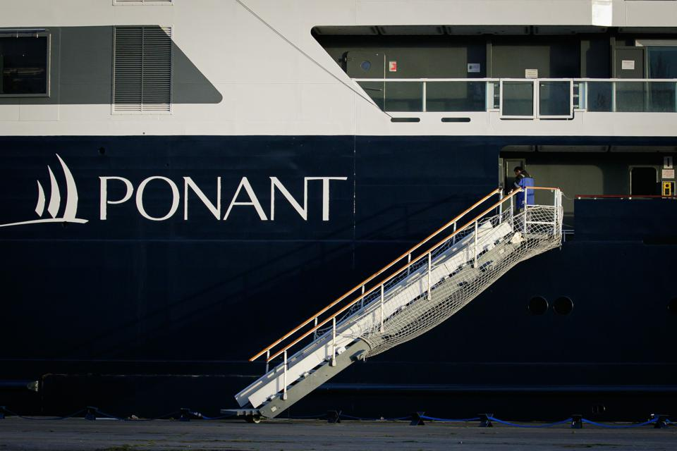 """The side of a navy blue and white PONANT cruise ship, with a stair gangway.  The word """"PONANT"""" is highlighted."""