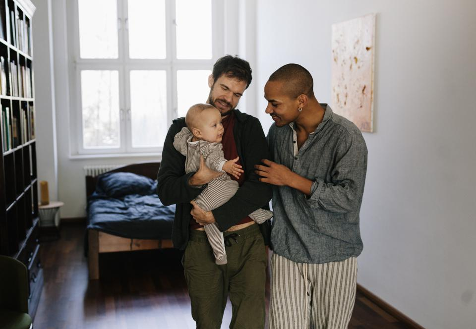 Gay fathers leaving bedroom together carrying newborn son. Father's are interacting with baby. Morning shot.