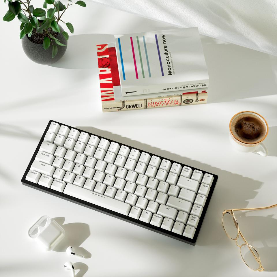 Vissles V84 mechanical keyboard on a table with some books and a cup of coffee