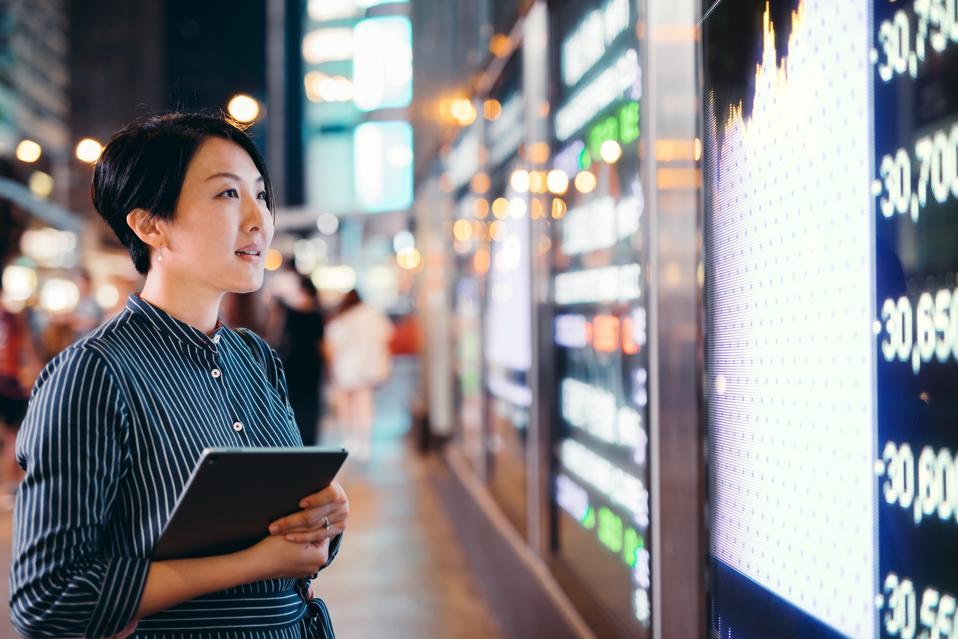 Businesswomen checking stock market data on display board