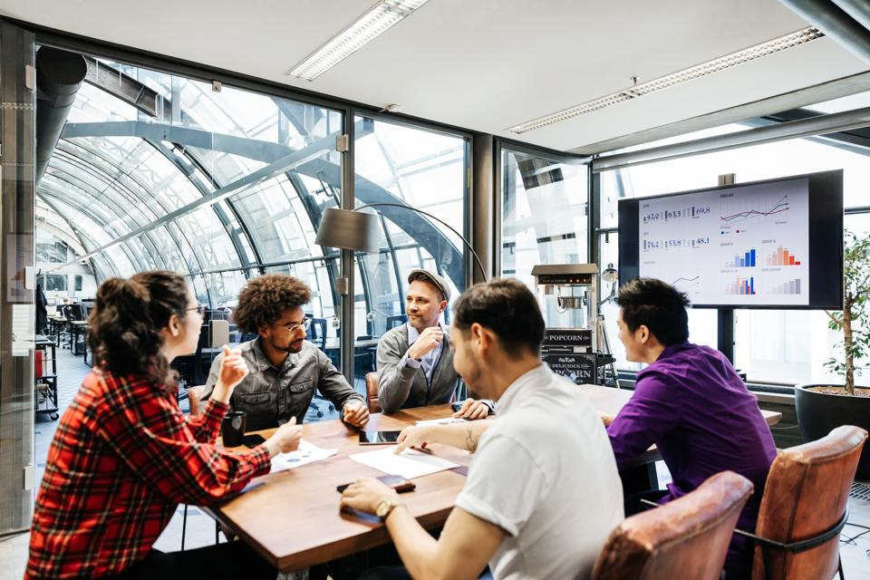 Team Leaders Sitting At Conference Table For Meeting