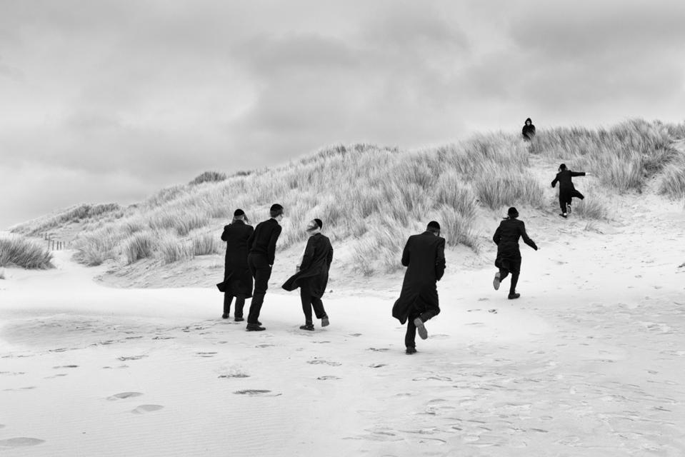 Men in black running in dunes