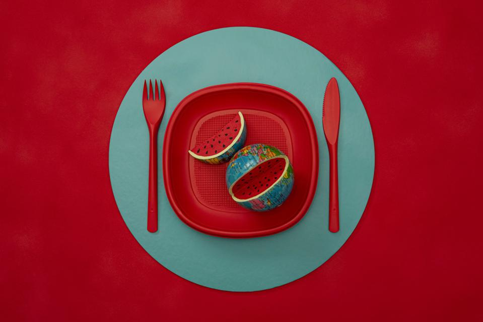 Still Life photo of red plate on green  base with  the world as food.