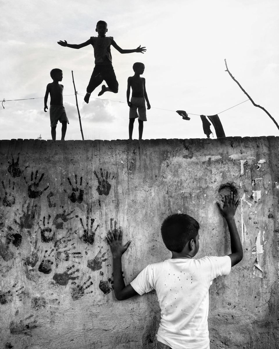 kids jumping on top pf wall decorated with hands silhouettes.