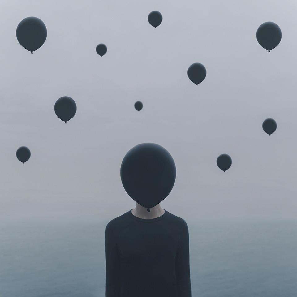 A person with face covered by a black balloon.