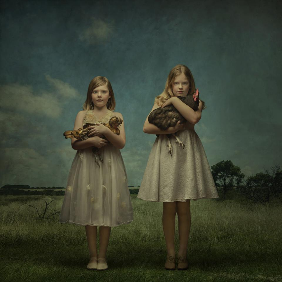 Two girls, each holding a chicken in her arms.