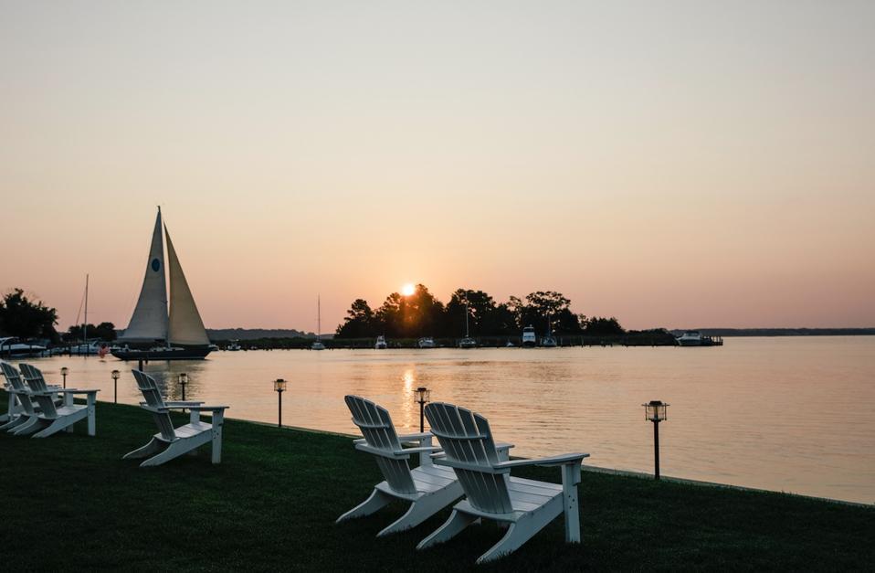 Les chaises Adirondack font face à la rivière Miles à l'Inn at Perry Cabin alors qu'un voilier passe
