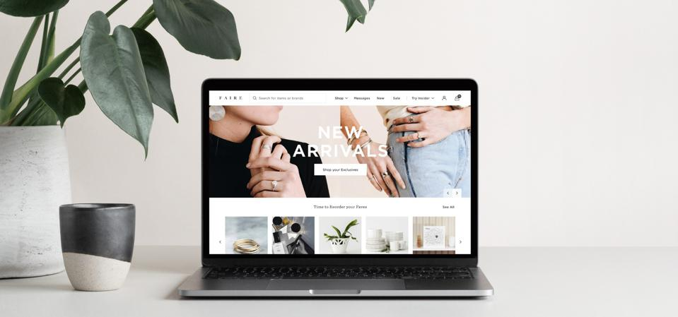 The homepage of the Faire online wholesale marketplace on a laptop on a desk with a houseplant.