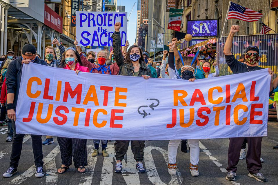 A crowd of climate activists marching behind a banner. A...