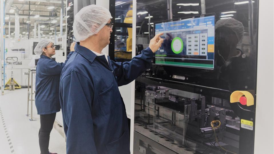 Dois operários de fábrica interagindo com uma célula robótica.