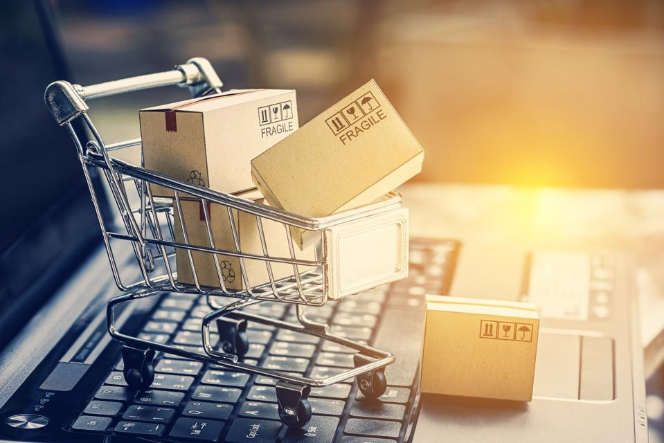 جعبه های کاغذی در سبد خرید روی صفحه کلید لپ تاپ.  ایده های مربوط به تجارت الکترونیکی ، تجارت الکترونیکی یا تجارت الکترونیکی معامله خرید یا فروش کالا یا خدمات بصورت آنلاین از طریق اینترنت است.