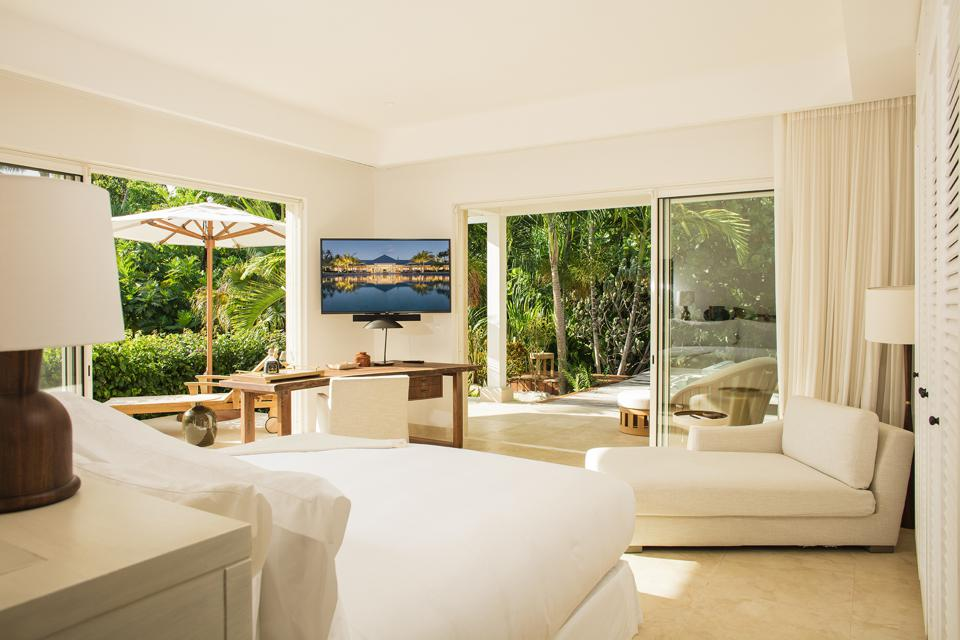 An all-white contemporary bedroom with sliding doors leading to the tree filled outdoors