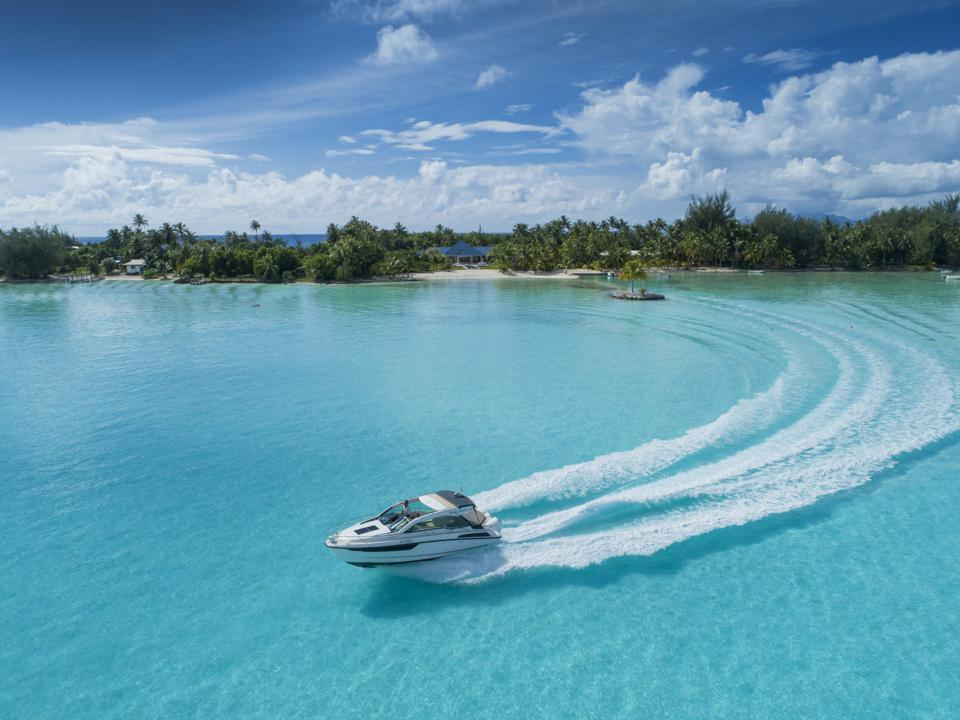 A motorboat skimming across turquoise water