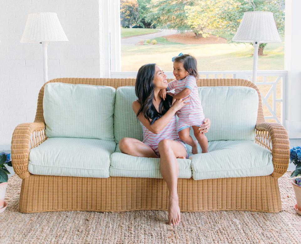 A woman sitting with a cute child on a rattan sofa with a rug.