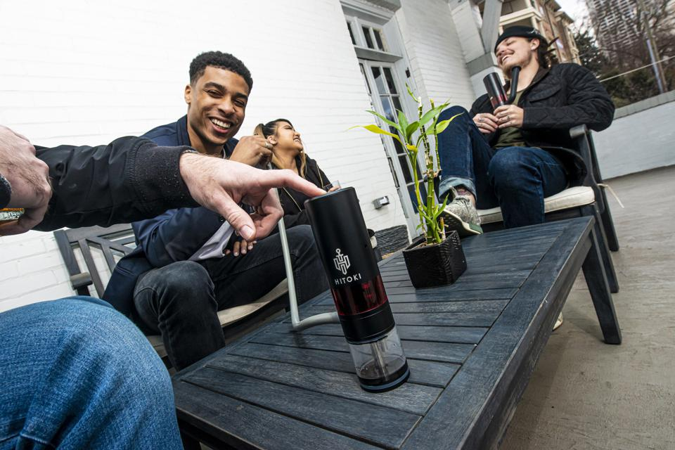 A group of friends enjoy cannabis with the laser-fired Hitoki Trident bong.