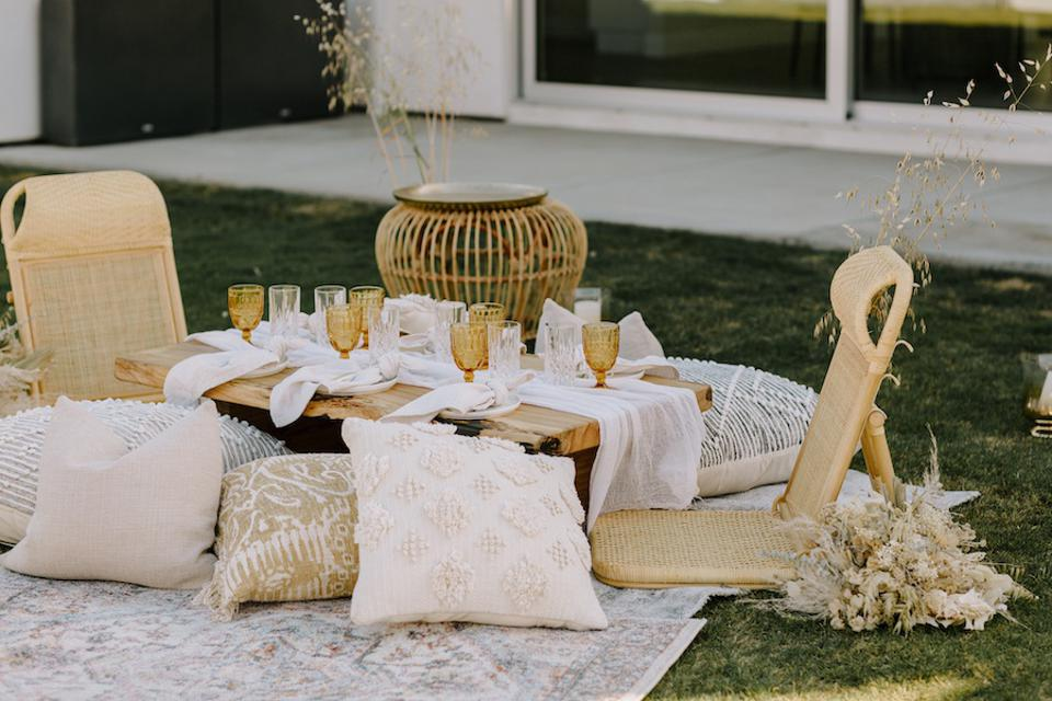 a picnic scene with rattan chairs, a set table and pillows