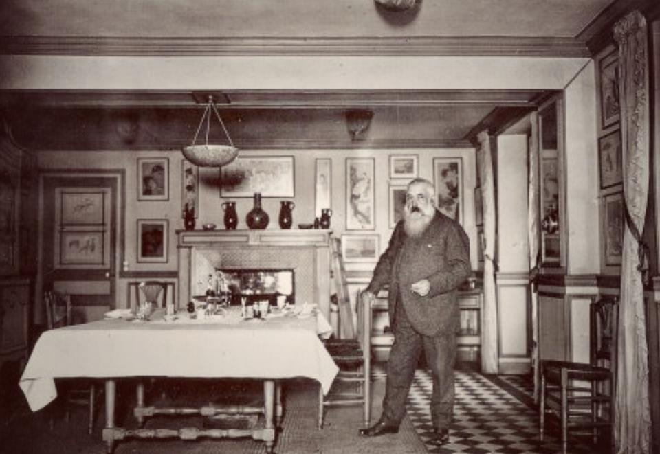Claude Monet in the dining room at Giverny; the table is set with wine bottles and glasses