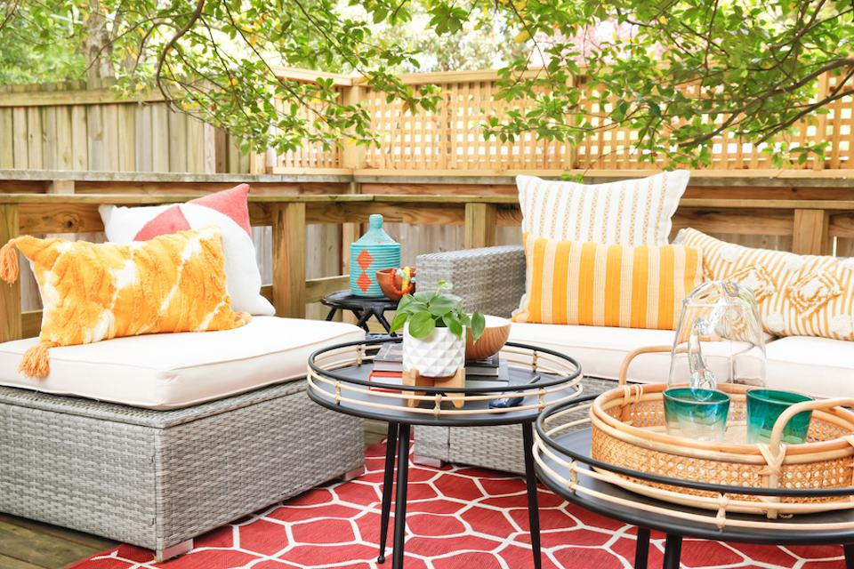 An outdoor living room with yellow and white pillows