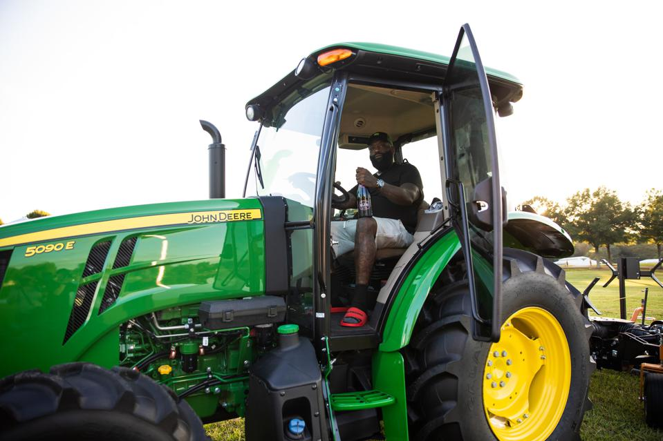 Rapper Rick Ross sits on a John Deere tractor and prepares to mow the lawn at his 235-acre Fayetteville, Georgia, estate.