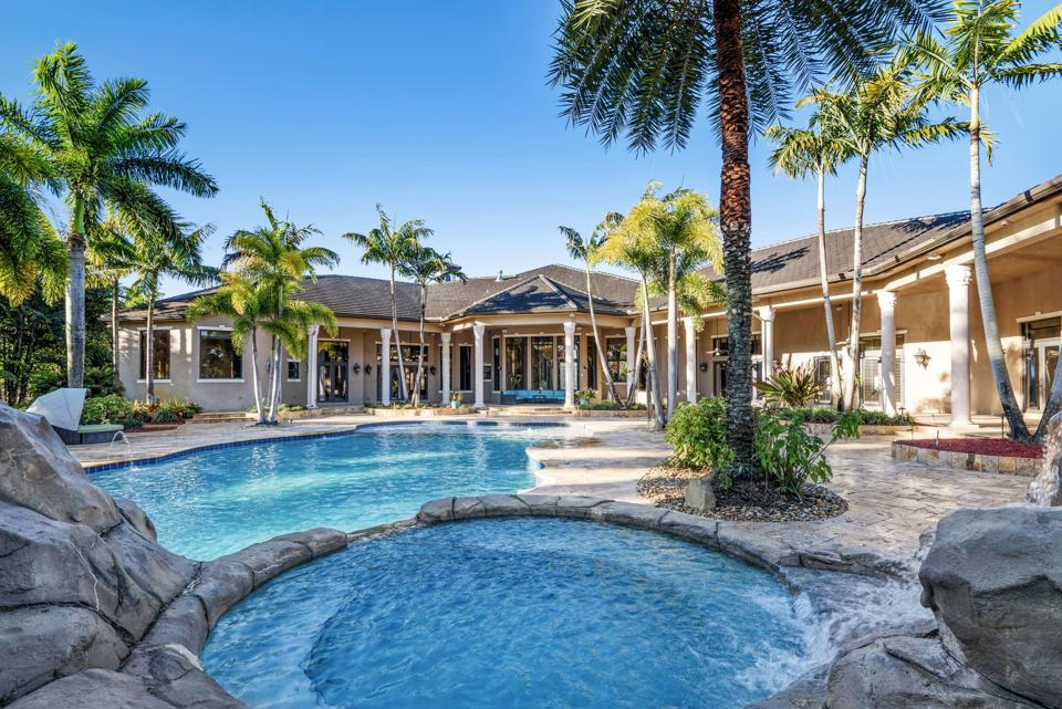 A Florida backyard features a waterfall and the waterslide.