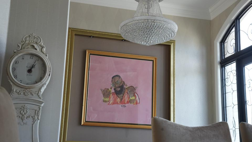 A pink image of rapper Rick Ross sits on a wall near a chandelier and a wall clock.