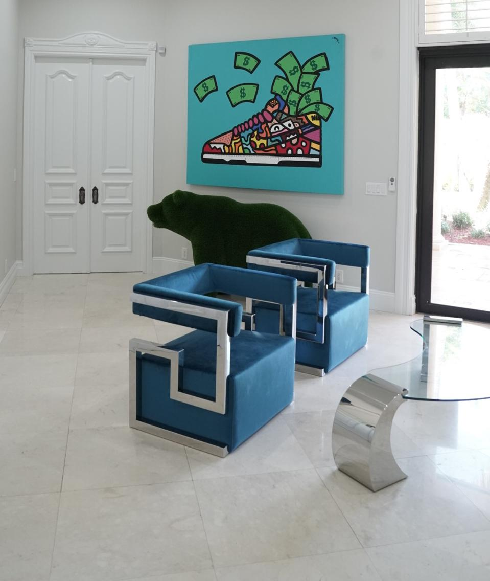 A white room features colorful art and unique furnishings.