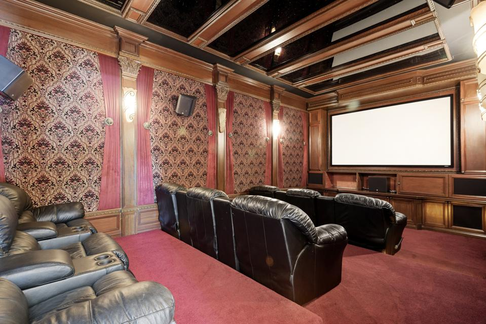 A home cinema has seating and a large movie screen.