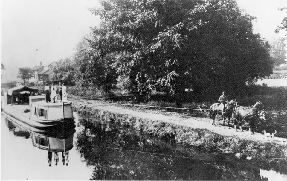 A boat in a canal being pulled by two horses.
