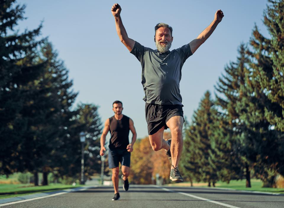 The old and young sportsmen running on the road