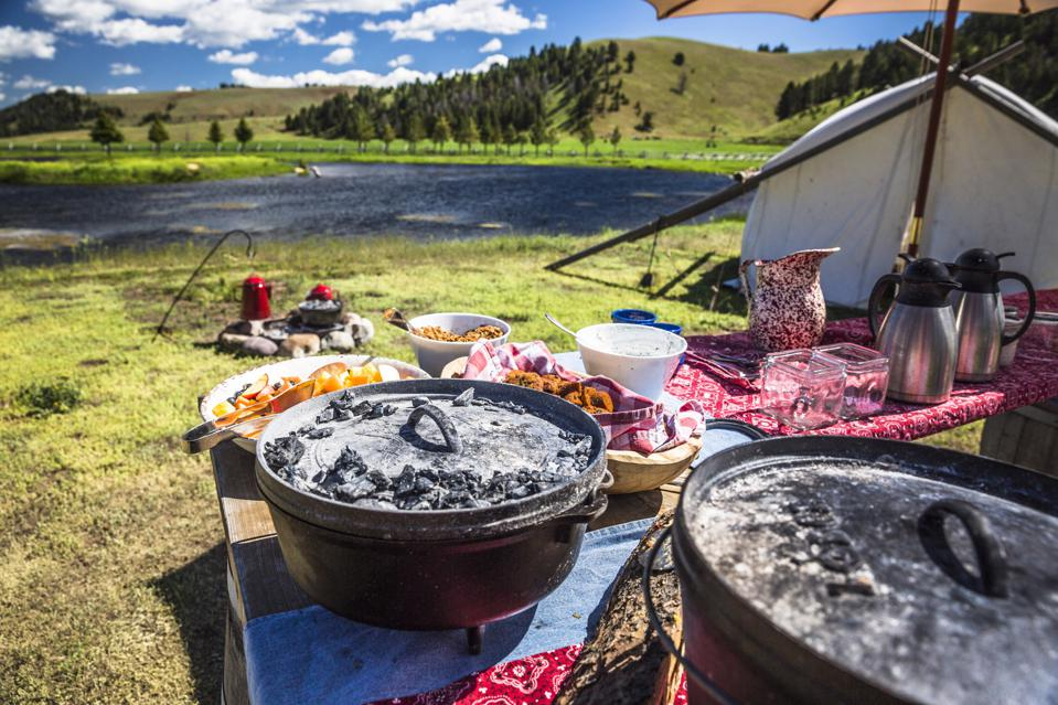 dutch ovens on picnic tables with tent and pond