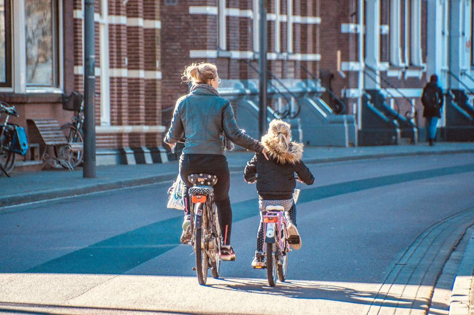 A mother and her young daughter, each on bikes, are seen cycling down a paved pathway