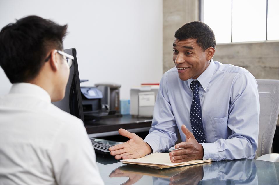Profesional masculino de raza mixta en reunión con joven asiático