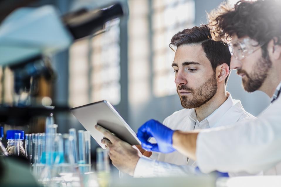 deux scientifiques utilisant une tablette numérique en laboratoire