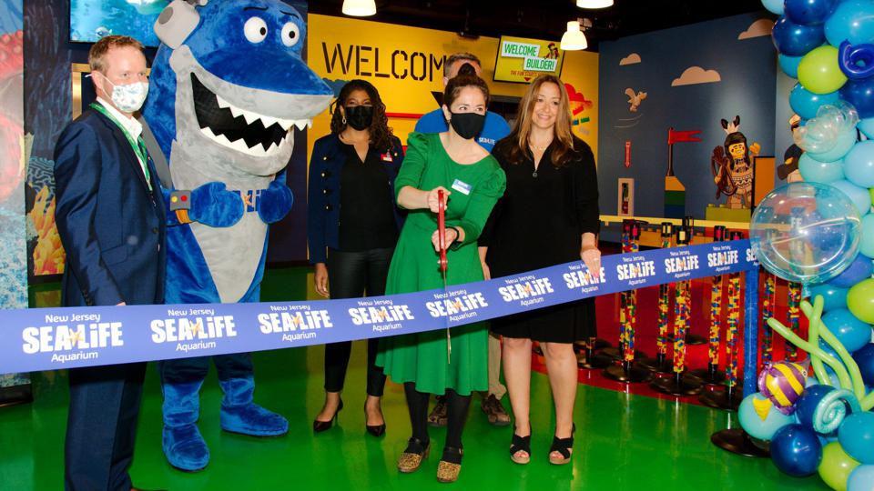 Camille DePascale.  Managing Director of New Jersey Sea Life Aquarium and Legoland Discovery Center New Jersey cuts the ribbon at the grand opening ceremony, along with American Dream COO, Nicole Mozeliak.