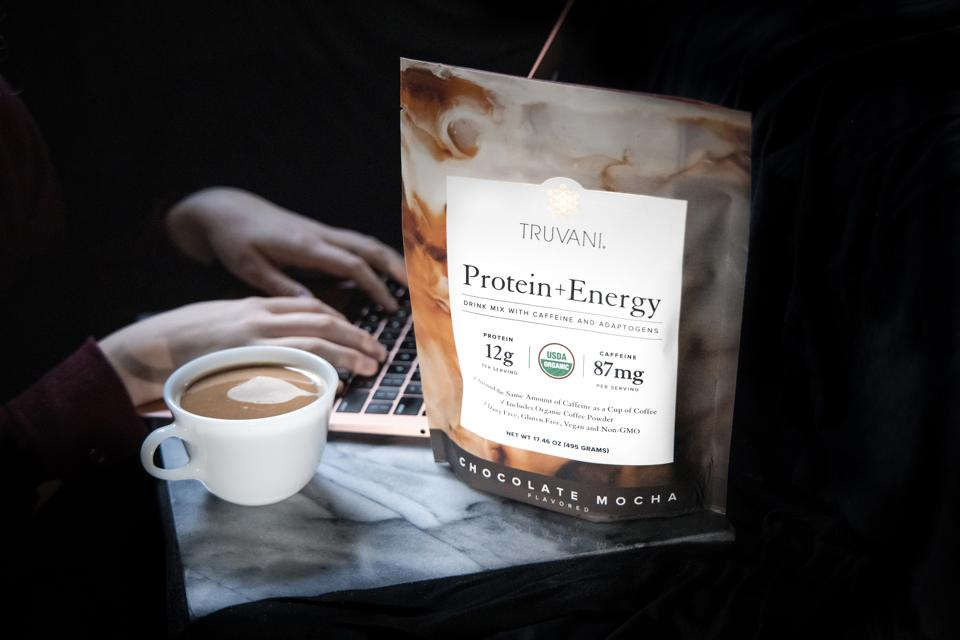 A Truvani Protein + Energy bag sits next to a cup of coffee and computer.