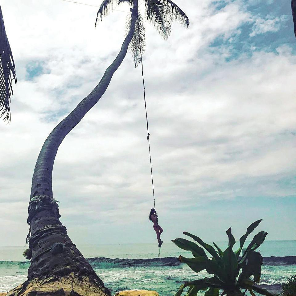 A person swinging on a rope near the ocean.