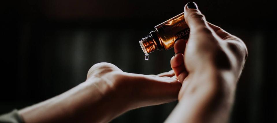 One hand pouring an essential oil into the other hand.