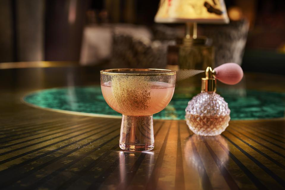 The Stepford Wife Cocktail is a twist on the French75 cocktail in a beautiful pink glass with gold dust glistening up the side accompanied with an edible Parfum.