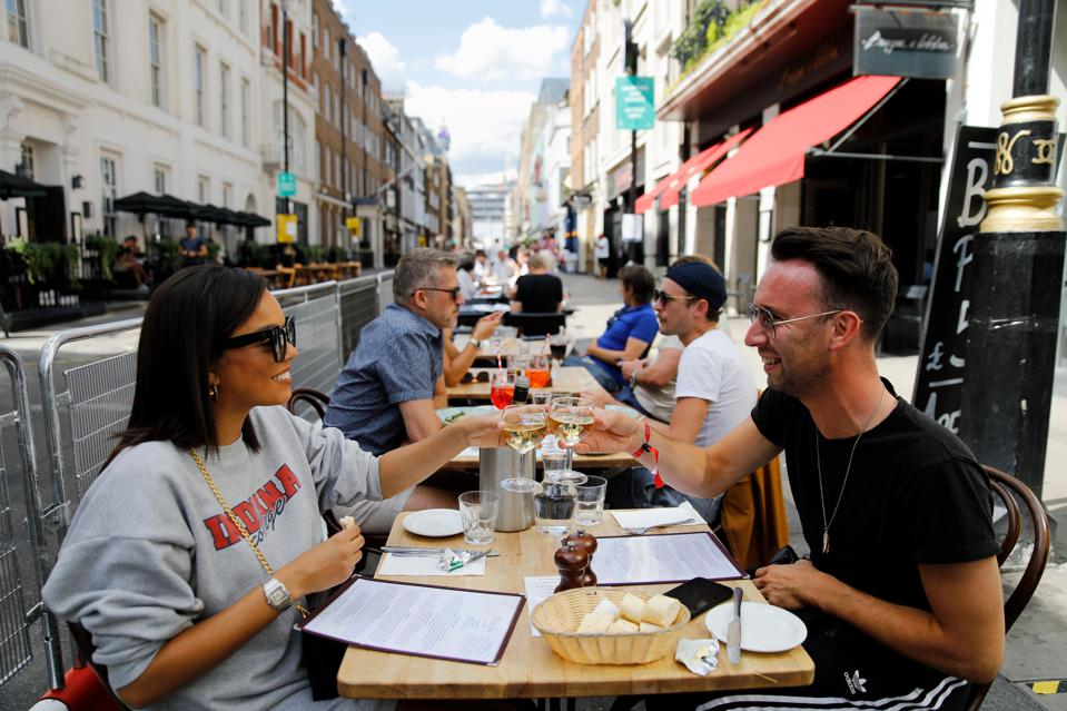 Diners enjoy their drinks as they sit at tables outside a restaurant in London on August 3, 2020, as the Government's ″Eat out to Help out″ coronavirus scheme to get consumers spending again gets underway. - Britain's ″Eat out to Help out″ scheme began Monday, introduced last month by Chancellor Rishi Sunak to help boost the economy claw its way from a historic decline sparked by the coronavirus crisis. (Photo by Tolga AKMEN / AFP) (Photo by TOLGA AKMEN/AFP via Getty Images)