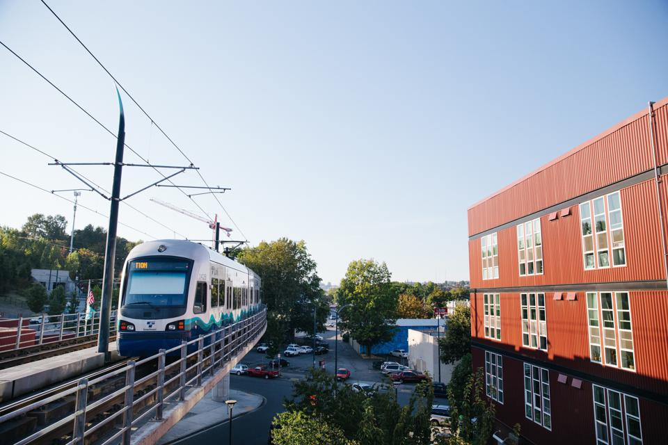 Train traveling by multifamily housing building