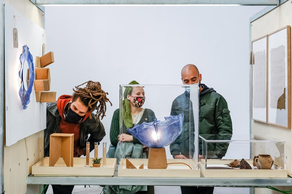 Three people looking at a display of products created from unique materials.