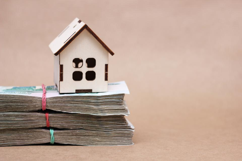 A small wooden house in on the bundles of 1000 thousandth Russian ruble notes. The idea of buying a property.
