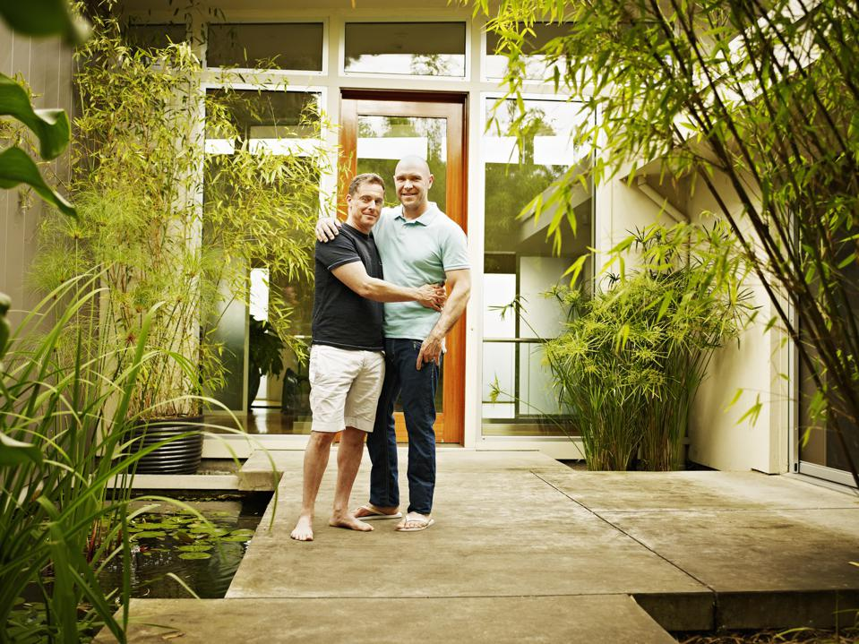 Smiling gay couple in front of contemporary home