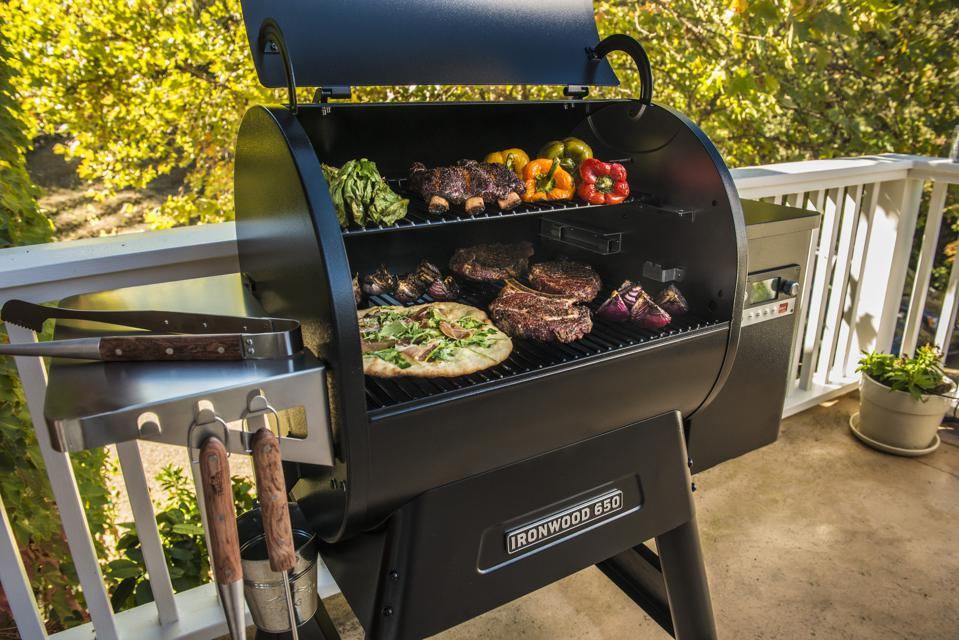 You can cook all your favorite foods on a pellet grill and it is especially designed to smoke regional barbecue including brisket, ribs and pulled pork. Foods including pizza, peppers, beef ribs and steak are shown photographed on an open Traeger pellet grill.