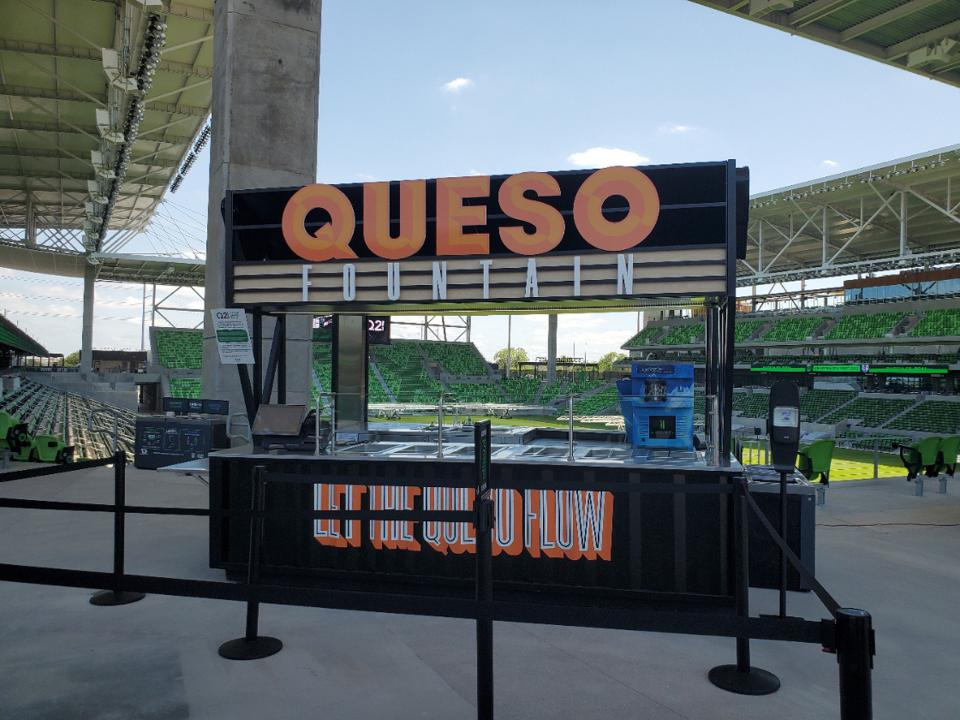 Queso fountain concession stand with view of the stadium pitch.