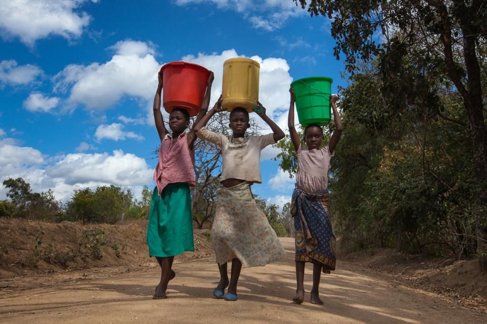 Girls carrying water buckets at a borehole in Malawi