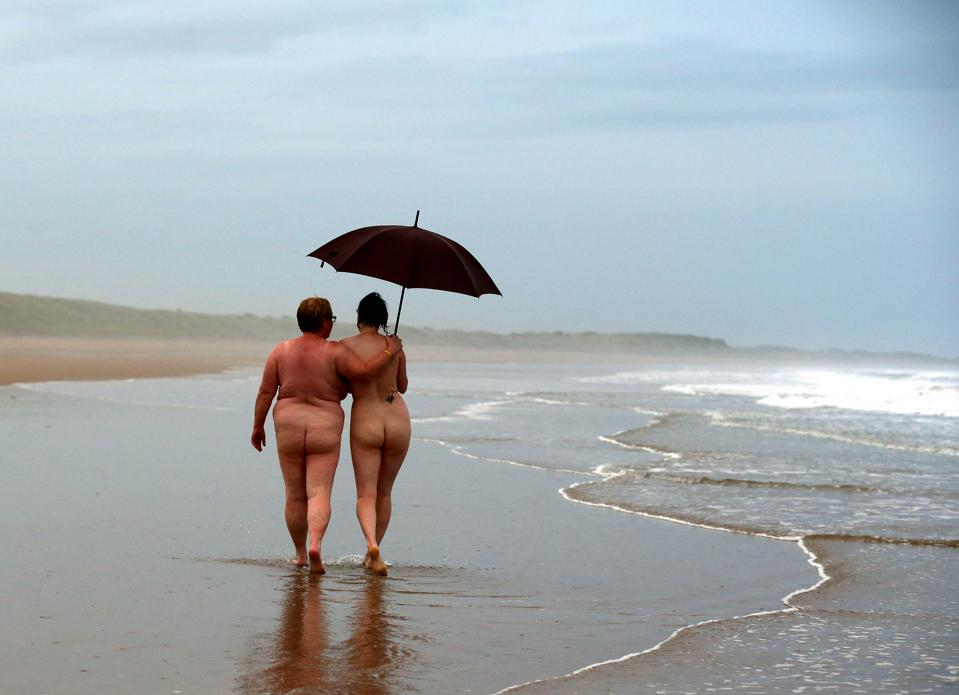 Naked couple walking by the beach