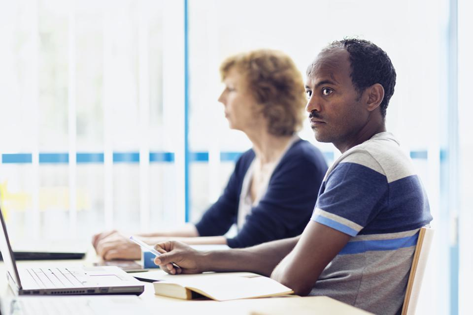 african refugee learning language in computer lab