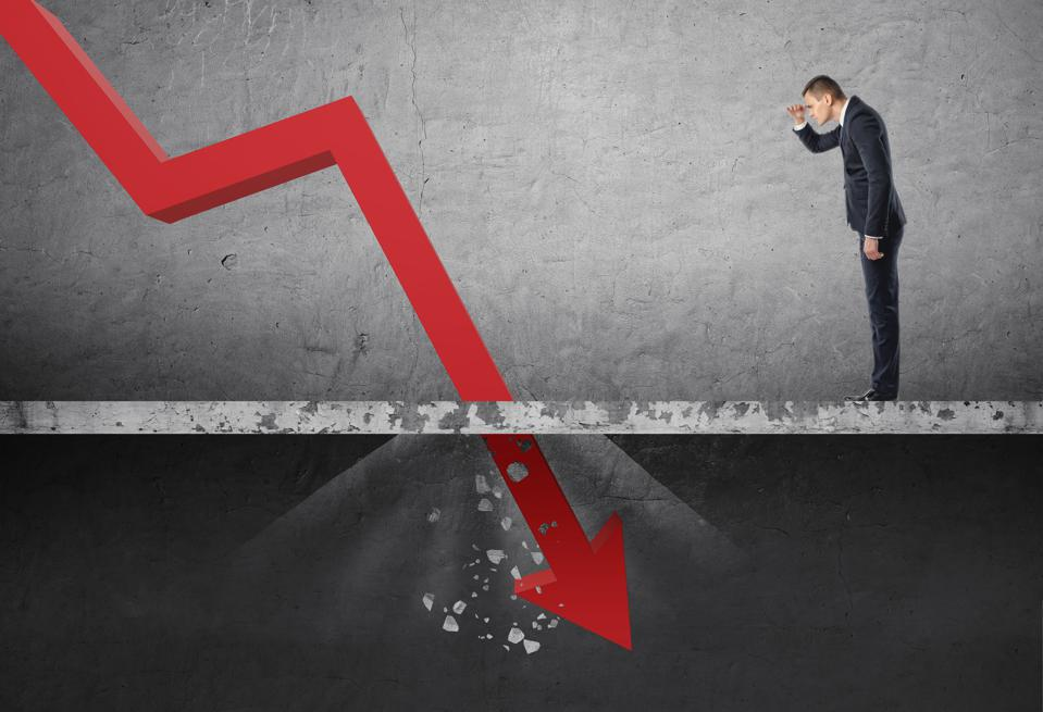 Businessman looking down at the falling red arrow destroying a